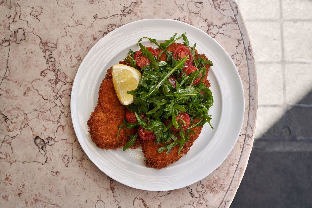 breaded chicken with a garnish of rocket salad and tomatoes