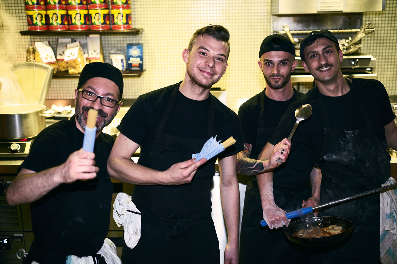 kitchen staff holding fresh pasta